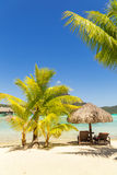 Two sunlounger chairs under a thatched parasol on a sand beach w. Ith a view on the lagoon and Mount Otemanu on the tropical island of Bora Bora, near Tahiti, in Stock Photo