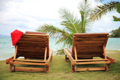 Two sunloungers with Santa hat standing on a beach Royalty Free Stock Photography