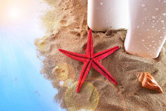 Two sunscreen on sand with starfish and shell on table Royalty Free Stock Images