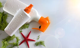 Two sunscreen spray with starfish on glass table top view Stock Image
