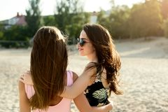 Two suntanned friends sunbathing on the beach and having fun. Girls wearing stylish swimsuits and sunglasses enjoy in. Two suntanned friends sunbathing on the Royalty Free Stock Image