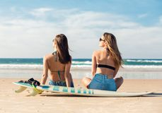 Two surfer girls at the beach stock image