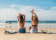 Two surfer girls at the beach. Two beautiful surfer girls at the beach with arms open Royalty Free Stock Photo