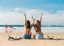 Two surfer girls at the beach. Two beautiful surfer girls at the beach with arms open stock photo