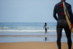 Two surfer guys going to the ocean ready for surf session Royalty Free Stock Images