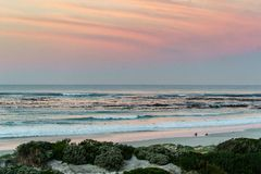 Two surfers sitting on Betty`s Bay beach at sunset in the Western Cape, South Africa royalty free stock images