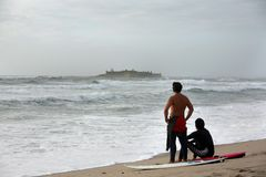 Two surfers. Looking to the castel in the island Stock Images
