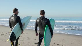 Two surfers on the beach near the Santa Monica Pier. stock video footage