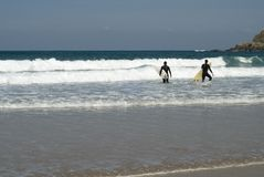 Two surfers entering the water. Walking Royalty Free Stock Photos