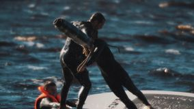 Two surfers fighting with soft bats standing on surfing board in wavy water stock footage