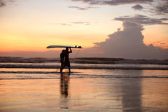 Two surfers on the ocean beach at sunset. A couple of surfers walking by the ocean at sunset holding a surfing board Stock Photography