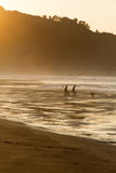 Two surfers sit on the shore of the ocean watching the sunset. Stock Photography