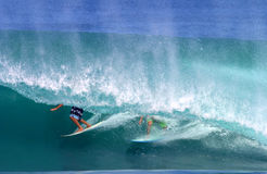 Two Surfers Surfing in One Tubing Wave. Two surfers riding deep in a tubing wave at Backdoor surf break on the island of Oahu, Hawaii Royalty Free Stock Images