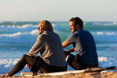 Two surfers talking on the beach Stock Photography