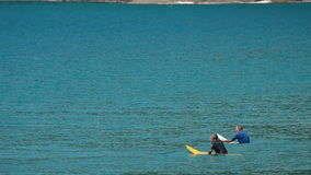 Two surfers waiting for big waves stock footage