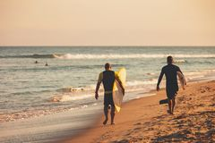Two surfers walking down the beach with their surfboards. Two adult males with their surfboards walk on the beach in the sand towards a great surf spot in Malibu royalty free stock photography