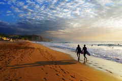 Two surfers walking on Sopelana beach. At sunset stock images