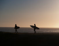 Two surfers walking towards the waves in the sunset Stock Photo