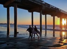 Two surfers walking under a beach pier, La Jolla, California, USA stock photos