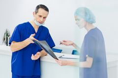 Two surgeons discussing x-ray and diagnosis. In hospital royalty free stock photo