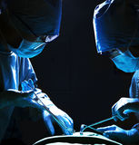 Two surgeons looking down, working, and holding surgical equipment with patient lying on the operating table Royalty Free Stock Image
