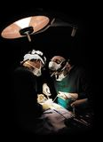 Two surgeons operating. Vertical orientation and dark background Royalty Free Stock Photo