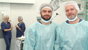 Two surgeons pose at the surgery room. Two caucasian surgeons of different ages posing at the surgery room. Bearded male doctors standing against background of stock video