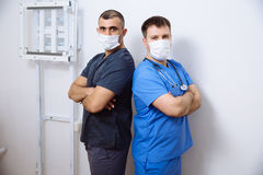 Two surgeons in sterile uniforms standing back to  with arms folded and looking camera on white background Stock Photos