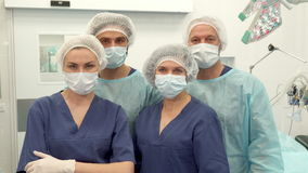 Two surgeons and two nurses pose at the surgery room. Two male surgeons and two nurses posing at the surgery room. Medical workers in uniform and procedure masks stock video