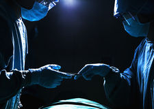 Two surgeons working and passing surgical equipment in the operating room, dark Royalty Free Stock Photos