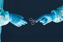 Two surgeons working and passing surgical equipment in the operating room Royalty Free Stock Image