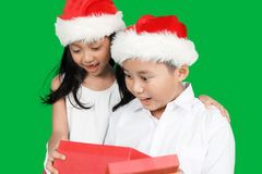 Two surprised children open Christmas gift. Portrait of two surprised children open a Christmas gift box together while wearing Santa hat in front of green Royalty Free Stock Photos