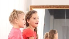 Two surprised girls. Against a mirror stock footage