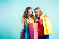 Two surprised and happy young women looking into shopping bags stock images