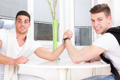 Two surprised men arm wrestling. Two surprised casual men arm wrestling Royalty Free Stock Images