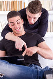 Two surprised smiling friends with laptop sitting on the couch Stock Image