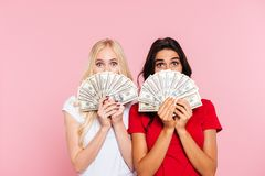 Two surprised women hiding behind the money. And looking at the camera over pink background stock photos