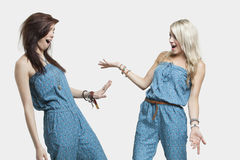Two surprised women wearing similar jump suits looking at each other over gray background Stock Image