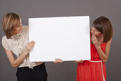 Two surprised women with white banner Stock Photo