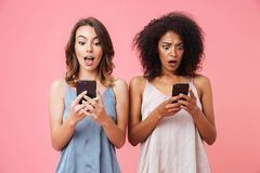 Two surprised young girls using mobile phones while standing. Isolated over pink background stock images