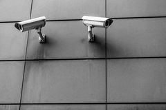 Two surveillance cameras. Black and white on the wall opposite each other Royalty Free Stock Image