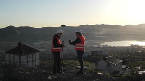Two surveyor in helmets performing geodesic measurements on top of the mountain stock video footage