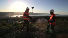 Two surveyor in helmets performing geodesic measurements on top of the mountain stock video