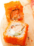 Two sushi roll with salmon and masago on the desk Royalty Free Stock Photography