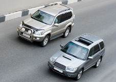 Two suv cars on road. Drives rides speed on road Stock Photography