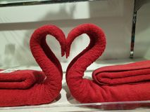 Two swans made of towels forming heart stock images