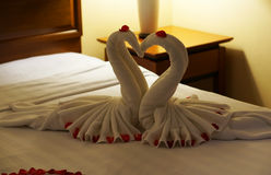 Two swans made from towels on honeymoon bed. For surprise wedding day Royalty Free Stock Photos