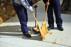 Two sweepers working, autumn leaves. Two sweepers sweeping the leaves of autumn, maintenance work, Spain Stock Photos