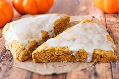 Two sweet autumn pumpkin scones with frosting Royalty Free Stock Photography
