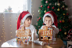 Two sweet boys, brothers, making gingerbread cookies house, deco Royalty Free Stock Image